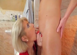 Short-haired blonde in red sucks her son's cock